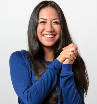 smiling woman with long dark hair with a blue sweater with her hands clasped