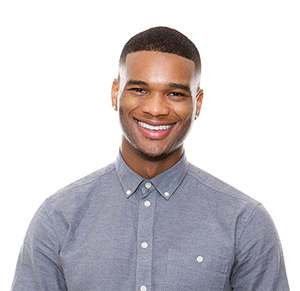 smiling man in front of transparent background wearing a dark gray buttoned up shirt