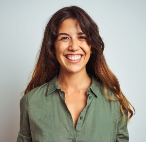 smiling woman in green buttoned shirt with brown hair