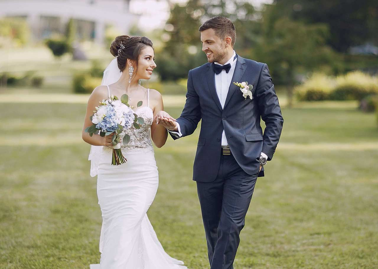 newlywed couple on their wedding day walking on the grass