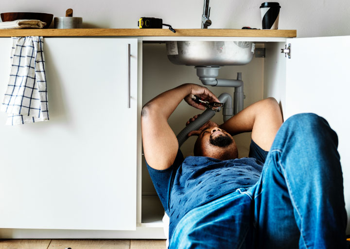 male in blue tshirt and blue jeans fixing something under the sink